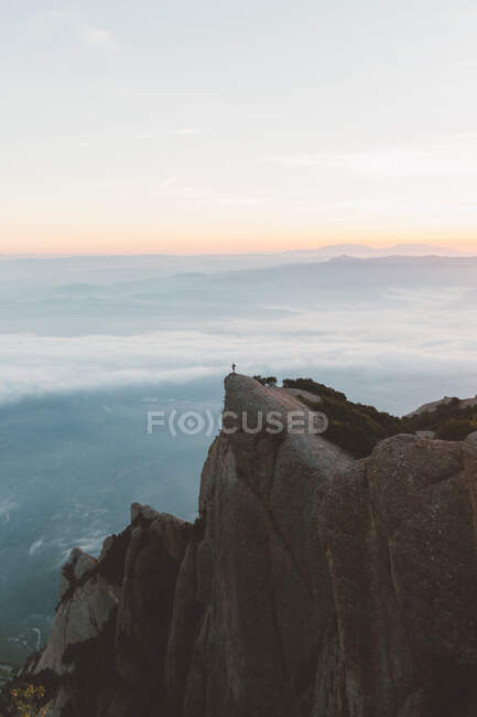 Persona anonima sulla scogliera durante l'alba — Foto stock