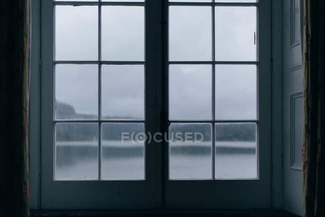 Ancora lago circondato da montagne sotto cielo limpido attraverso la finestra chiusa — Foto stock
