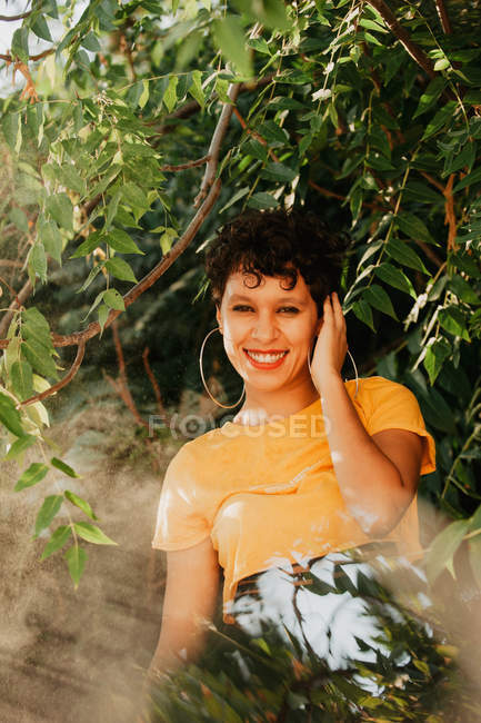 Portrait de brunette souriant avec commandes de cheveux courts en végétation verte avec la lumière du soleil — Photo de stock