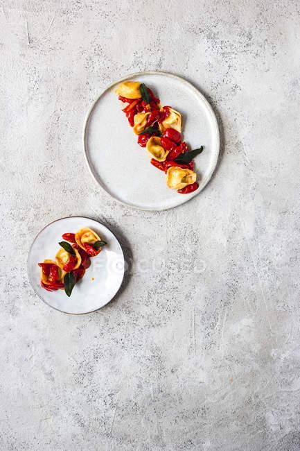 Вкусное блюдо тортеллини с помидорами на пластины на серый настольные — стоковое фото