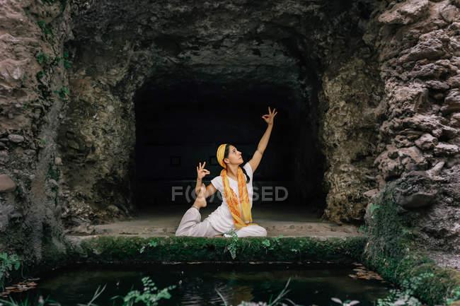 Mulher tranquila fazendo ioga perto de caverna de pedra — Fotografia de Stock