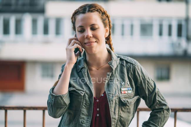Retrato de ruiva jovem com tranças falando no telefone celular ao ar livre — Fotografia de Stock
