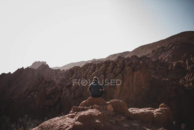 Задній погляд людини в футболках і штанях на крутій скелі і погляд на скелясту гору на тлі ясного безхмарного неба. — стокове фото