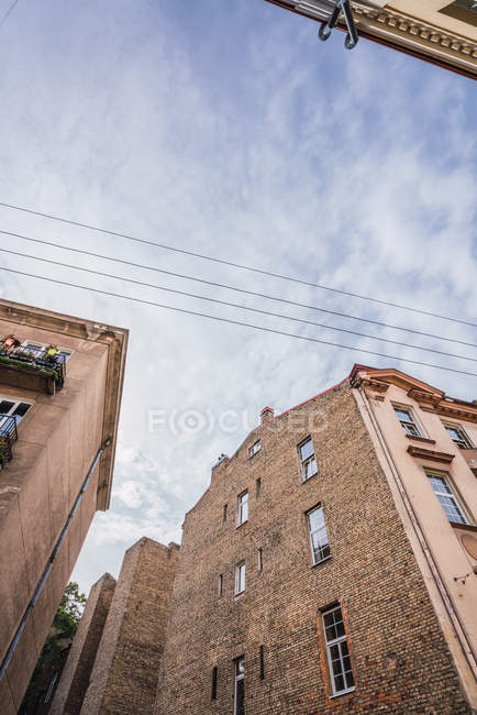 Brick buildings and electric wires against cloudy sky in old city — Stock Photo
