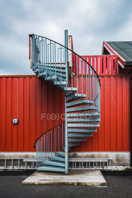 Winding metal staircase leading to house placed behind high red fence on background of cloudy sky — Stock Photo