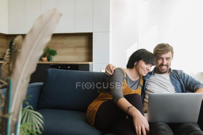 Молодой человек и женщина обнимают друг друга и наслаждаются хорошей пленкой на ноутбуке, сидя на удобном диване в уютной гостиной — стоковое фото