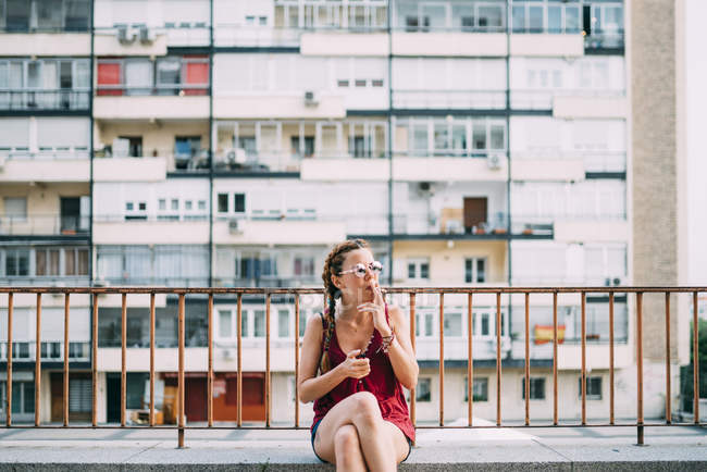 Red-haired young woman with braids and sunglasses smoking near railing against residential building — Stock Photo