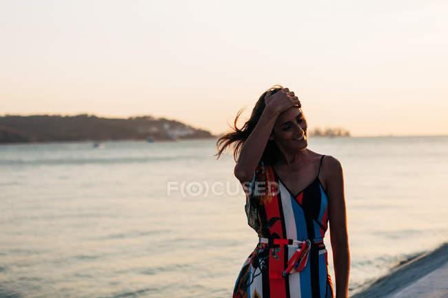 Laughing young woman in colorful summer dress standing on promenade at sunset — Stock Photo