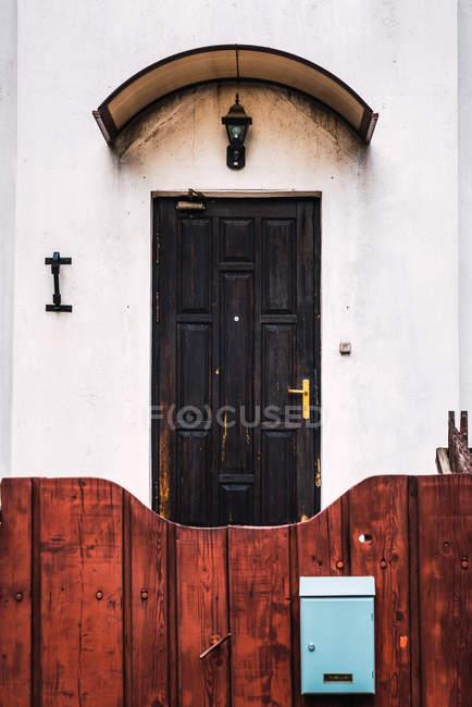 Recinto di legno pittoresca con piccola cassetta postale che si trova davanti casa suburbana con squallido porta — Foto stock