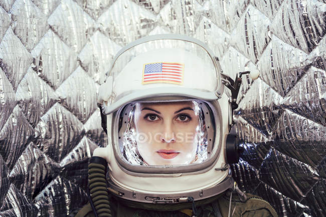 Confident girl wearing old space helmet with usa flag sign on foil background — Stock Photo