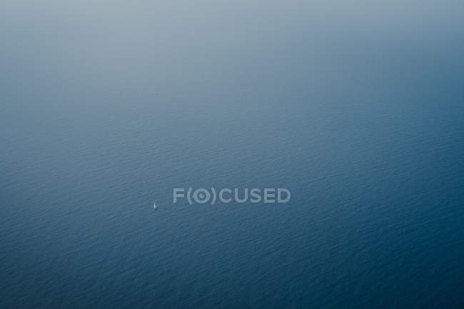 Aerial view of calm blue sea and distant floating little white boat — Stock Photo