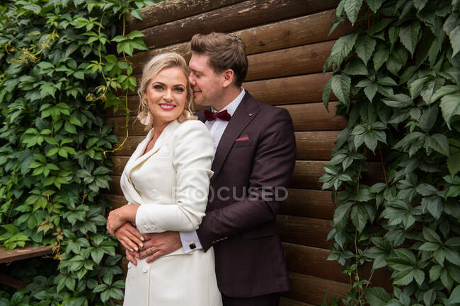 Elegant adult bride and groom embracing while standing in suits against wooden wall and smiling at camera — Stock Photo