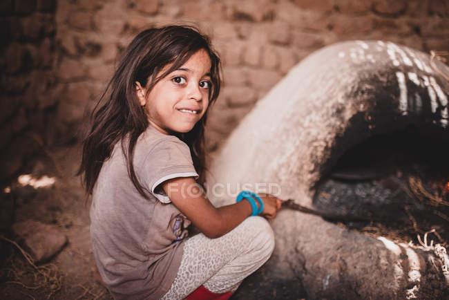 Bambina seduta sul pavimento in capanna e guardando la macchina fotografica, Marocco, Africa — Foto stock