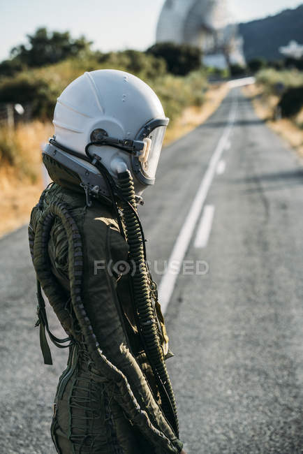Female astronaut in helmet and spacesuit standing on road in countryside — Stock Photo