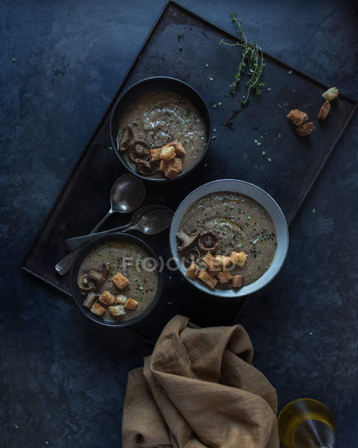 Mushroom cream soup with croutons in bowls on tray on dark background — Stock Photo