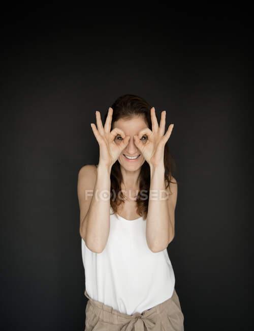 Bastante señora adulta en traje elegante alegremente sonriendo y manteniendo las manos cerca de la cara como máscara mientras está de pie sobre fondo negro - foto de stock