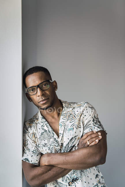 Portrait of casual black man leaning on white wall near window — Stock Photo