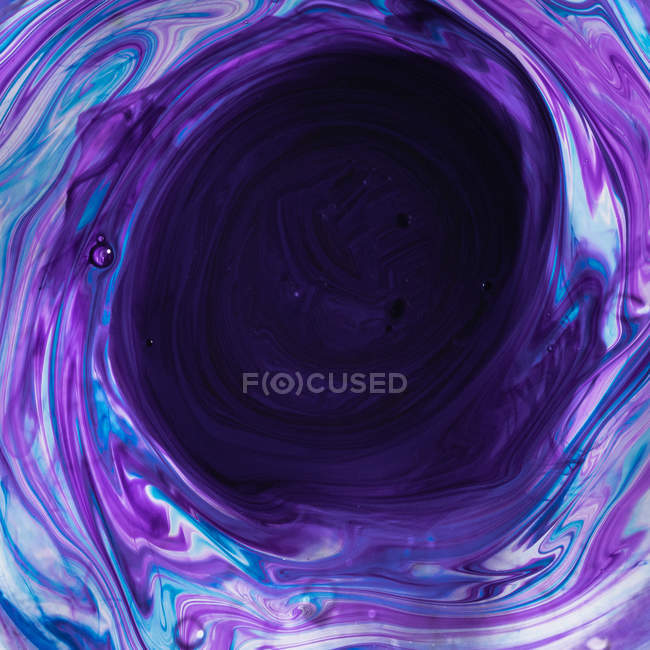 Swirls of dissolving blue and purple paint — Stock Photo