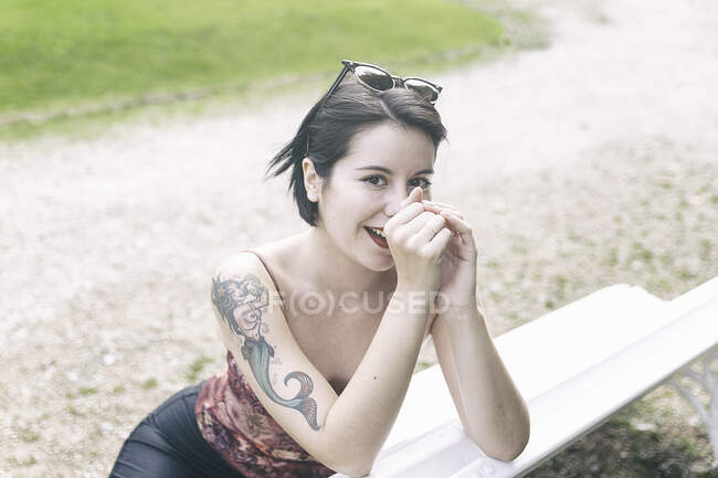 Attractive smiling woman with dark hair and tattoo on shoulder sitting on bench in park and looking at camera — Stock Photo