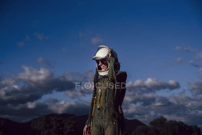 Smiling woman in astronaut costume and helmet standing against evening sky in nature — Stock Photo