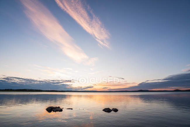 Surface of tranquil blue lake with dramatic sky at sunset — Stock Photo