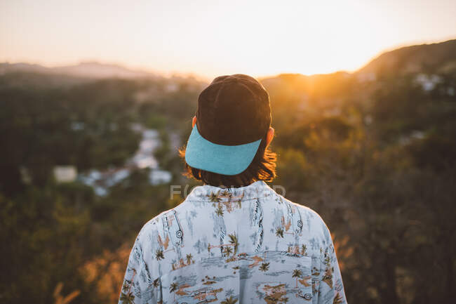 Back view of unrecognizable guy standing in nature and admiring view of magnificent sundown in Los Angeles, California — Stock Photo