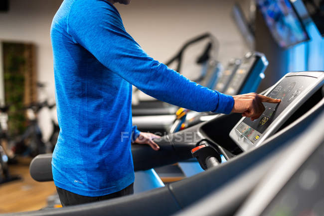 Close-up of athletic man jogging on treadmill in gym — Stock Photo
