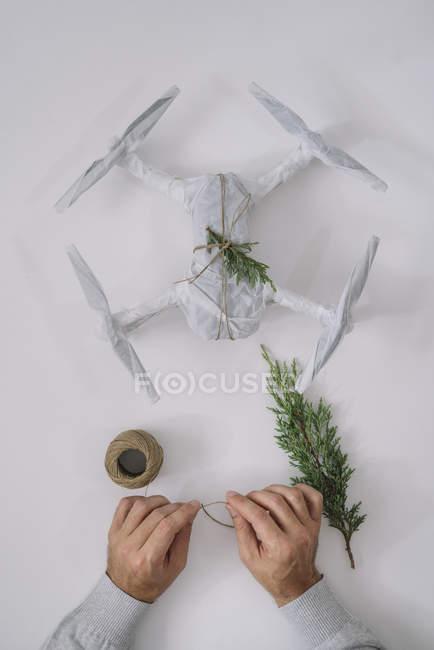 Mãos masculinas decoração embrulhado drone como presente de Natal com ramo de abeto e cordéis sobre fundo branco — Fotografia de Stock