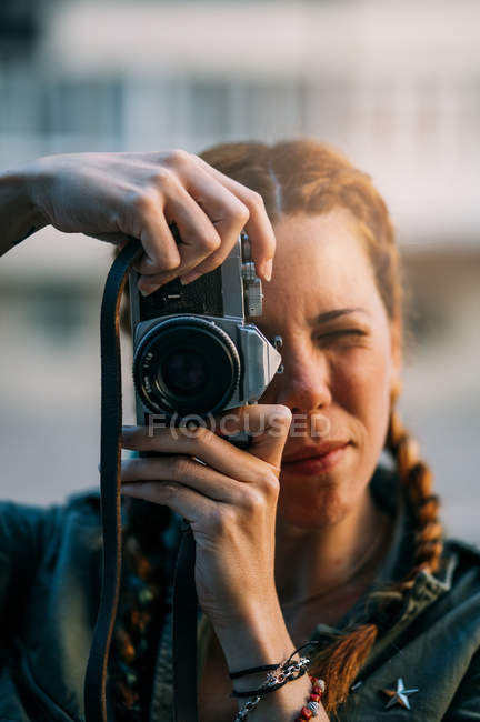 Portrait of redhead girl with braids taking photo with vintage camera — Stock Photo