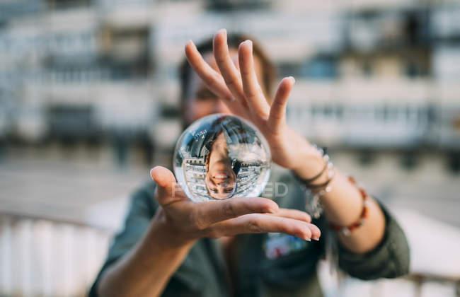 Женщина держит хрустальный шар с отражением в городе — стоковое фото