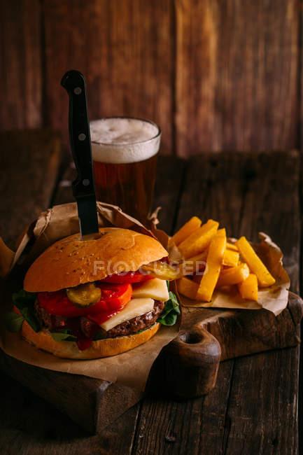 Вкусный гамбургер для гурманов с ножом на деревянной доске с пивом и картошкой фри — стоковое фото