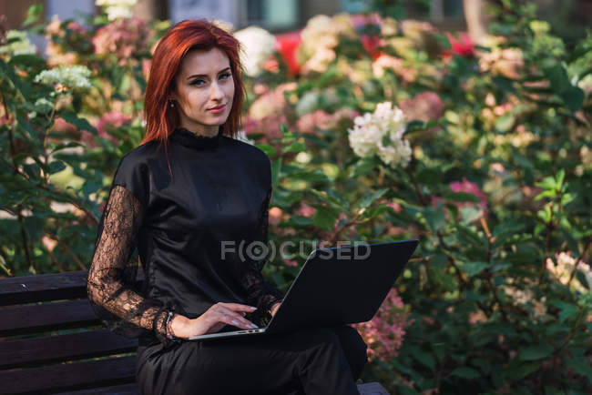 Portrait of young elegant woman using laptop on bench in park — Stock Photo