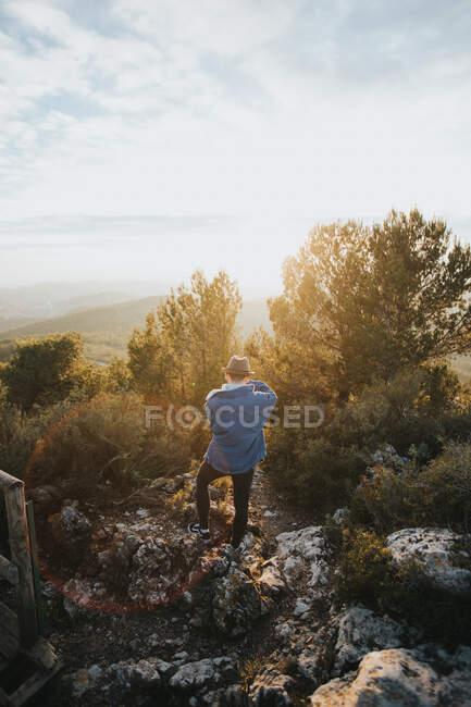 Вид сзади парня в случайном наряде, фотографирующего удивительную природу в солнечный день в Барселоне, Испания — стоковое фото