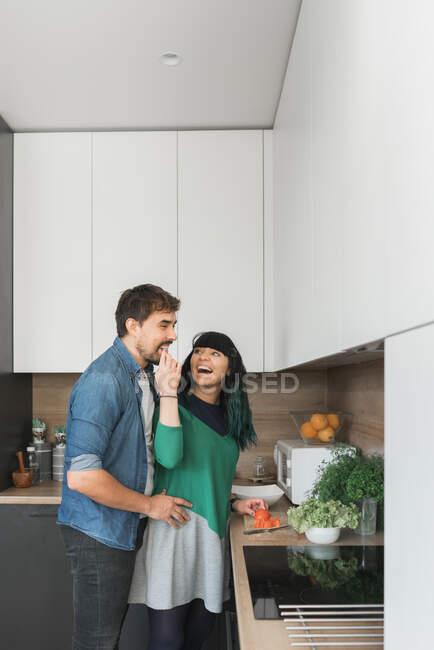 Alegre pareja de cocinar en la cocina juntos - foto de stock