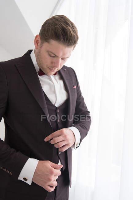 Vista lateral del joven hombre guapo de pie en el dormitorio blanco y ponerse el traje formal negro - foto de stock
