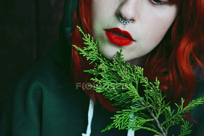 Close-up of young red haired woman holding fir twig — Stock Photo