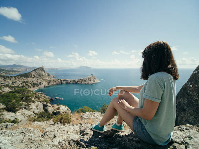 Pensive woman sitting on rocky coastline and looking at view — Stock Photo