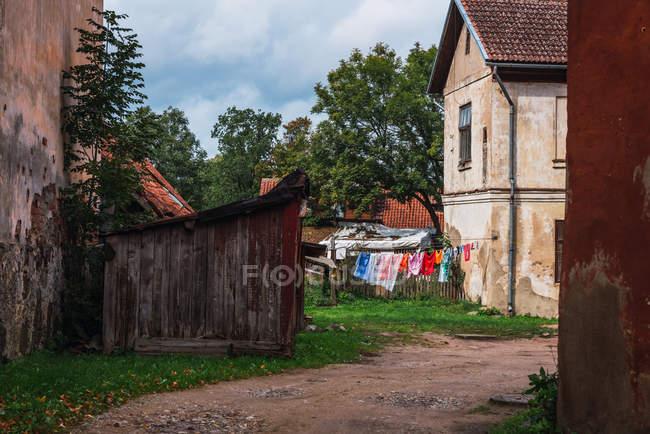 Красочная одежда, висящая на веревке во дворе среди потрепанных домов в маленьком поселке — стоковое фото