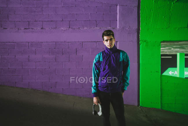 Young handsome man in sport jacket with headset standing on background of colorful wall and looking at camera — Stock Photo