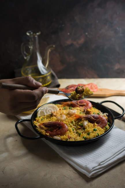 Main de l'homme maintenant fourche au dessus de la paella espagnole traditionnelle marinera avec riz, crevettes, calmars et moules en casserole — Photo de stock