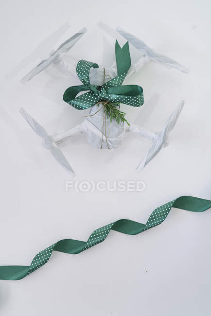 Drone wrapped as Christmas gift with green ribbon on white background — Stock Photo