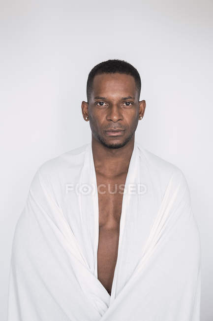 Portrait of confident black man wrapped in white sheet on white background — Stock Photo