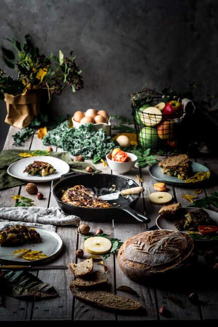 Зверху видніється смачний тортілья на сковороді біля тарілок зі шматочками, помідорами, фруктами, горіхами та листям на дерев