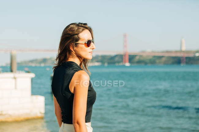 Young brunette woman standing on seafront and looking at view — стоковое фото