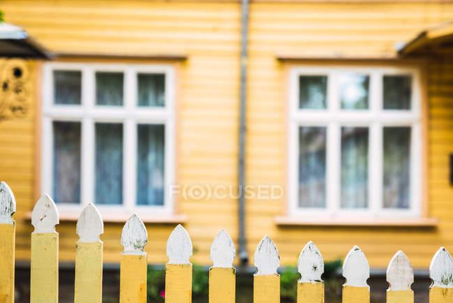 Живописный деревянный забор, окружающий двор на размытом фоне желтого загородного дома — стоковое фото