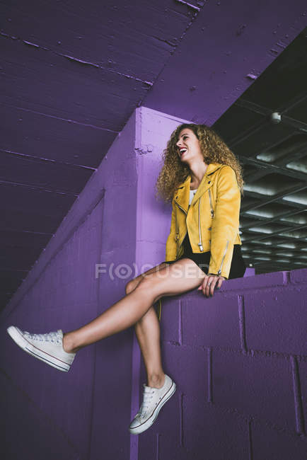 Stylish curly blonde in sneakers and yellow jacket sitting on purple wall and laughing — Stock Photo
