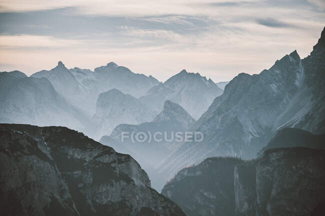 Thick clouds floating on sky over peaks of majestic mountain ridge in Dolomites, Italy — Stock Photo