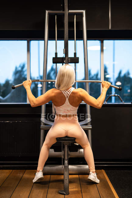 Athletic blond woman in sportswear doing exercise in gym — Stock Photo