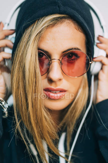 Young blond woman in black hoodie and round sunglasses with headphones looking at camera on white background — Stock Photo