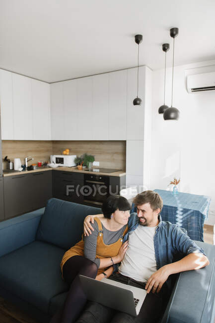 Young man and woman embracing each other and enjoying good film on laptop while sitting on comfortable sofa in cozy living room — Stock Photo